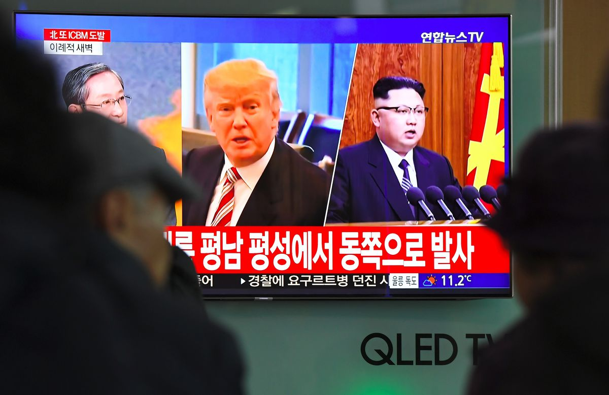 TOPSHOT - People watch a television news screen showing pictures of US President Donald Trump (C) and North Korean leader Kim Jong-Un (R) at a railway station in Seoul on November 29, 2017.