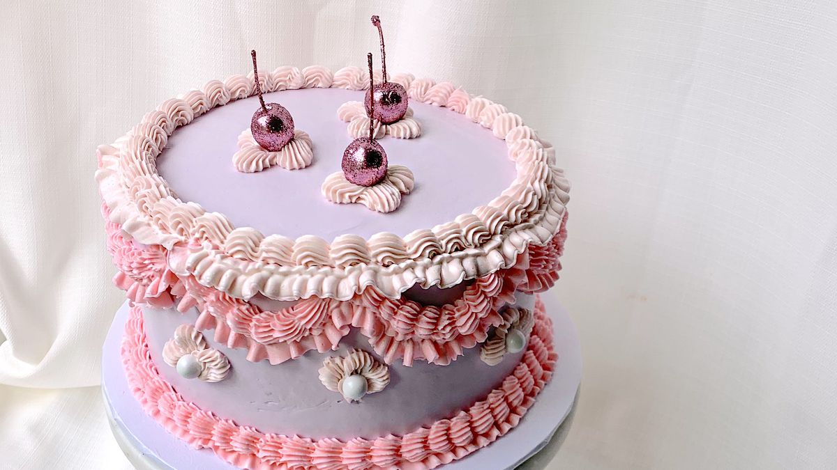 A round layer cake decorated with lavender, pink and beige buttercream, and topped with sparkly pink cherries.