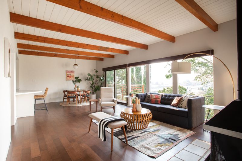Open room with a living area, dining area, and sliding doors to a wooden balcony.