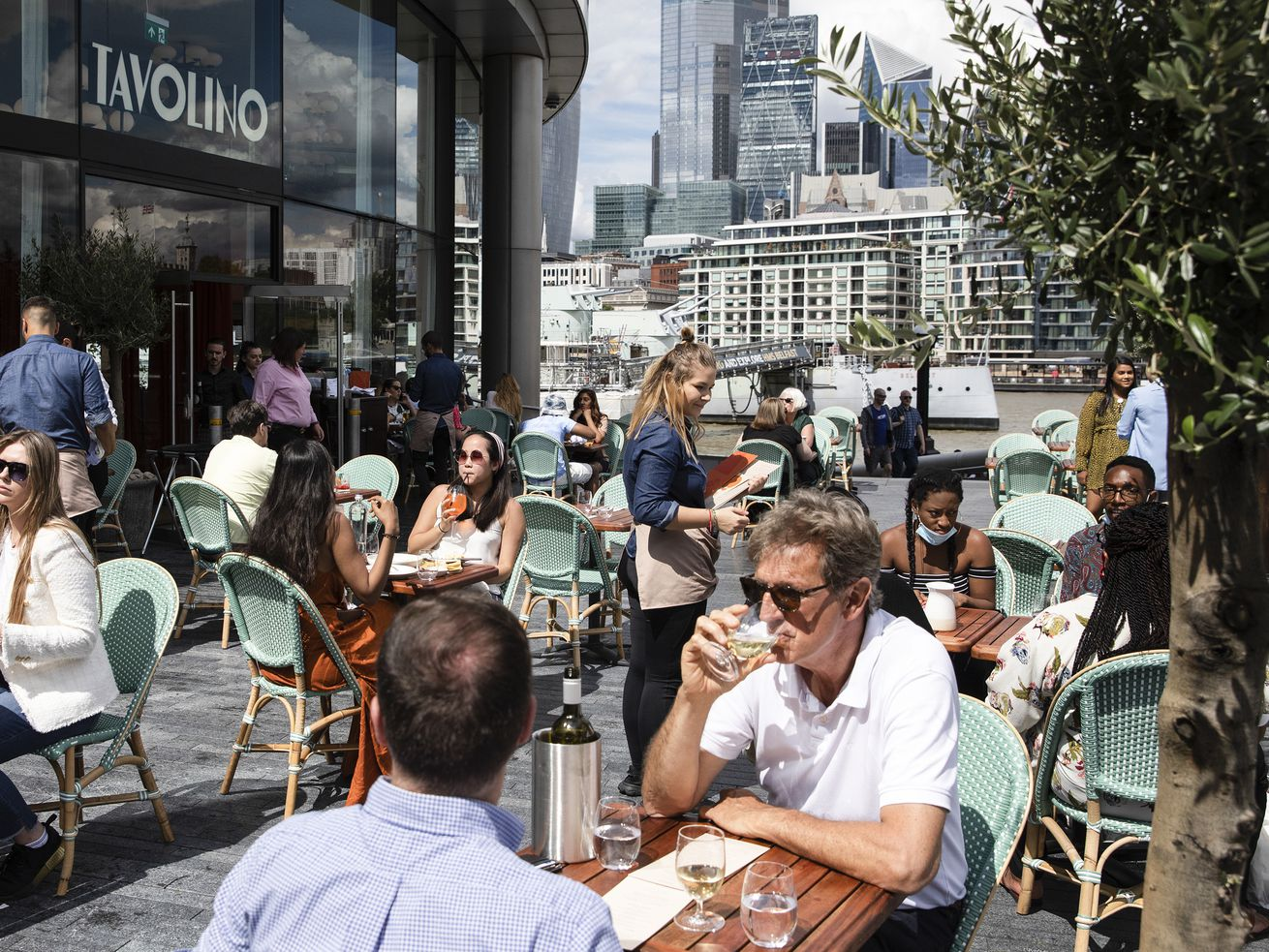 People sitting at outdoor restaurant seating on a London street.