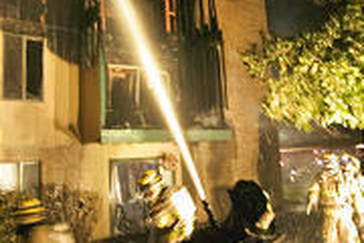 Firefighters drench flames at the Chelsea Park Apartments Tuesday.