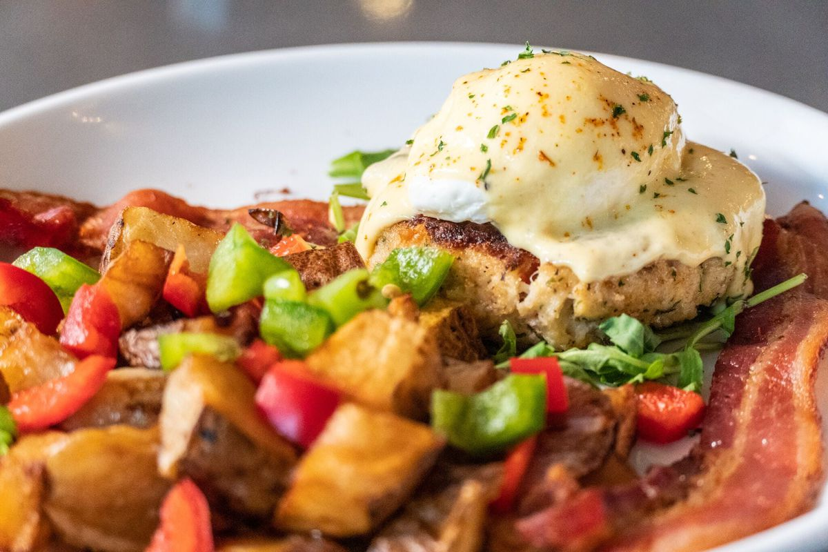 Crab cake eggs benedict with potatoes, peppers, and bacon