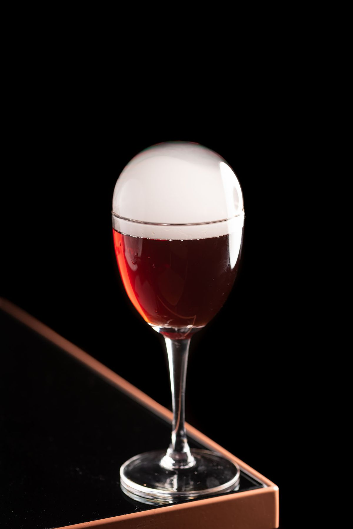 A deep red cocktail glass with a smoke foam dome on top.