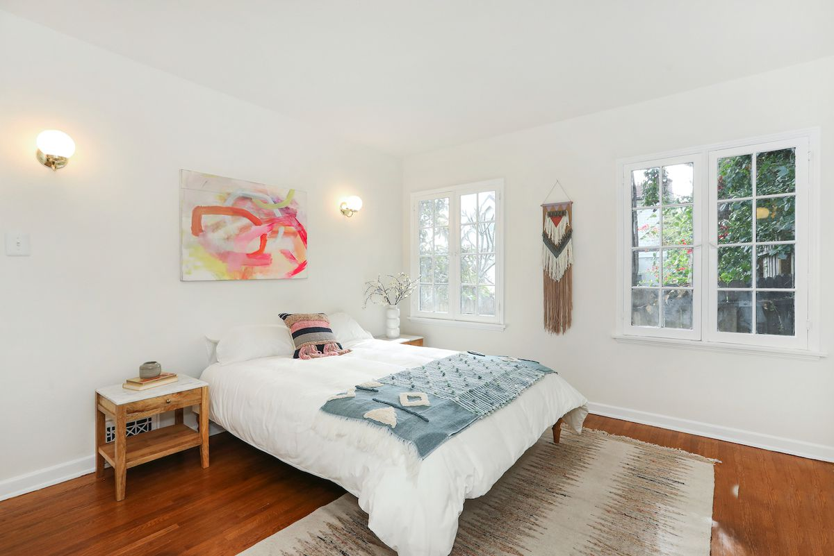 A bright ample room with wood floors and two sets of casement windows.