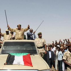 """Sudanese President Omar al-Bashir, center, waves from the back of a truck during a visit to North Kordofan, Sudan, Thursday, April 19, 2012. The Arab League said Thursday it would hold an emergency meeting over the increasing violence between Sudan and South Sudan. Sudan President Omar al-Bashir on Wednesday threatened to topple the South Sudan government after accusing the south of trying to take down his Khartoum-based government. Al-Bashir continued his hardline rhetoric on Thursday in an address to a """"popular defense"""" brigade headed to the Heglig area. The ceremony was held in al-Obeid, in northern Kordofan."""