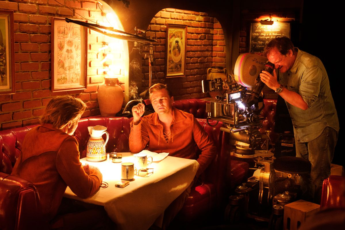 Quentin Tarantino stands behind the camera, shooting Leonardo DiCaprio and Brad Pitt at a restaurant table for Once Upon a Time …in Hollywood.