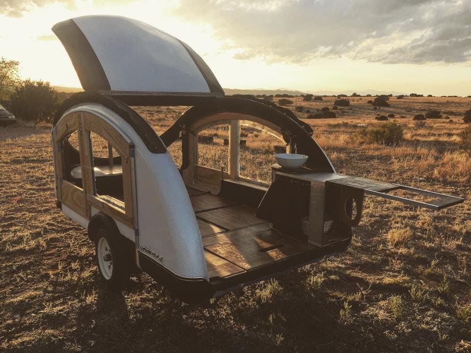 Best teardrop campers - The Earth Traveller trailer with its roof retracted on an open field.