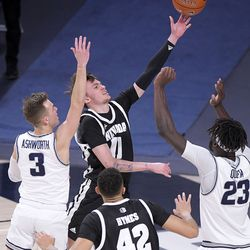 Nevada guard Kane Milling (11) takes a shot as Utah State guard Steven Ashworth (3) and center Neemias Queta (23) defend during the first half of an NCAA college basketball game Sunday, Feb. 28, 2021, in Logan, Utah.