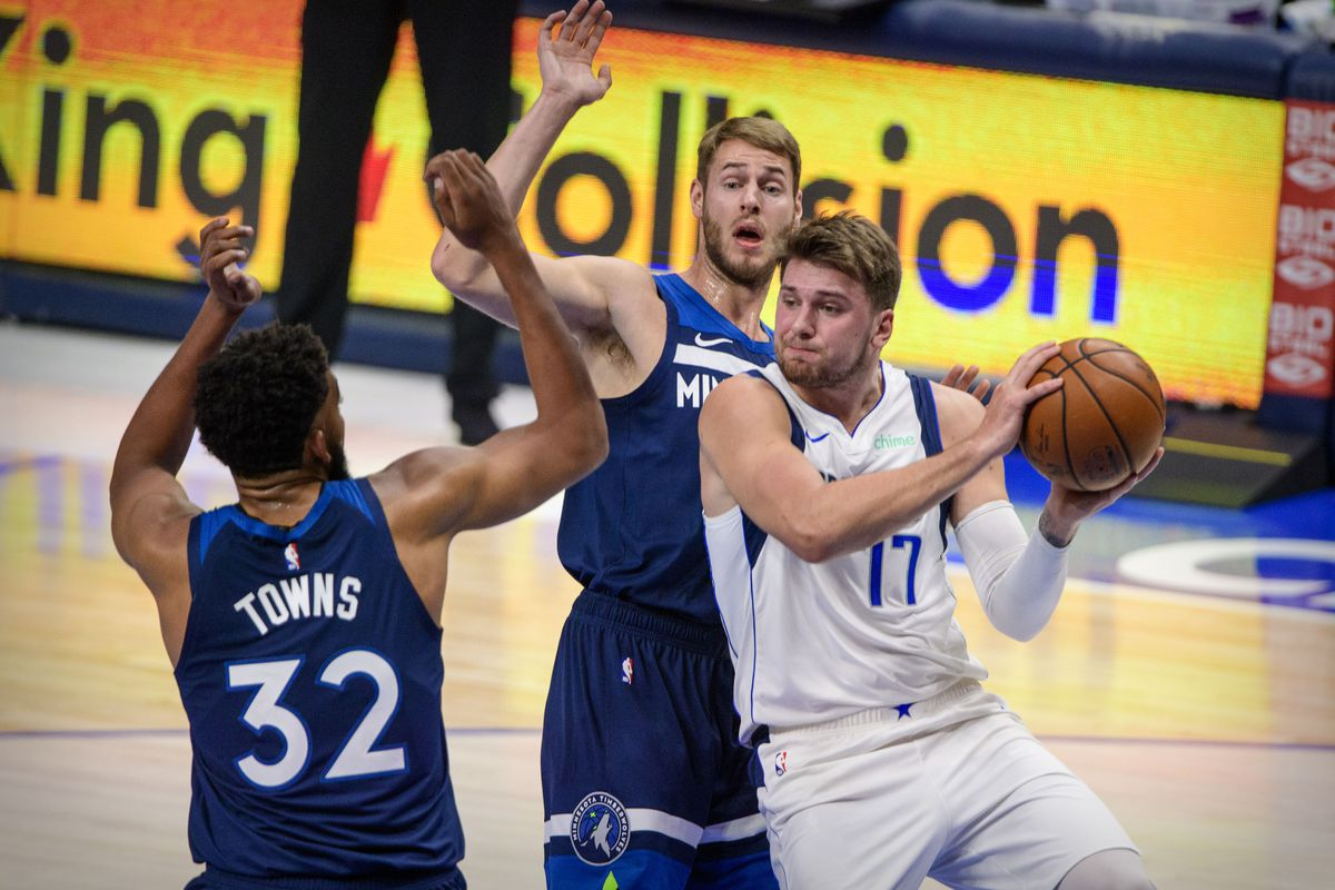 Minnesota Timberwolves center Karl-Anthony Towns and forward Jake Layman defend against Dallas Mavericks guard Luka Doncic during the first quarter at the American Airlines Center.