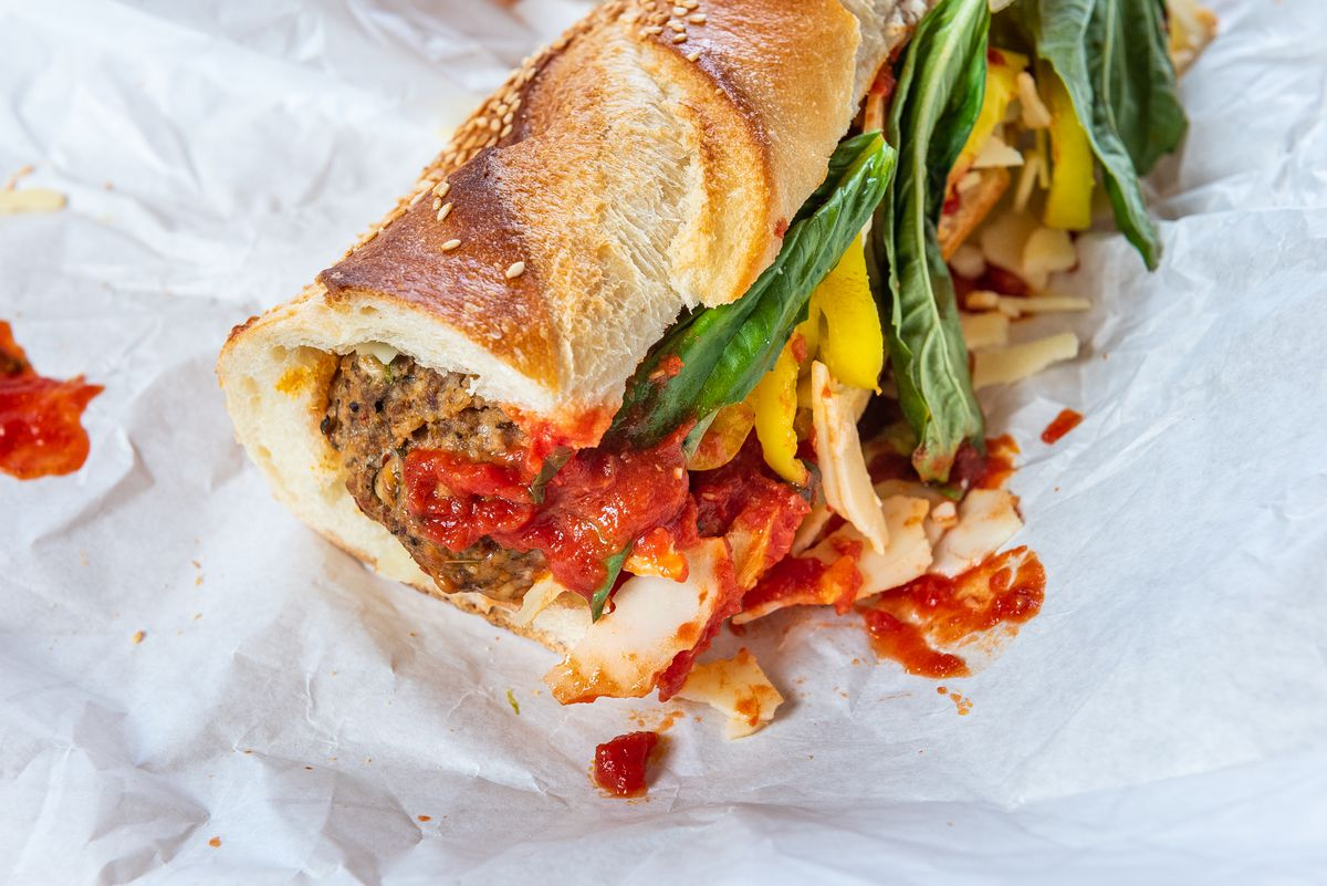 A close-up of a saucy meatball sandwich with green basil and yellow peppers