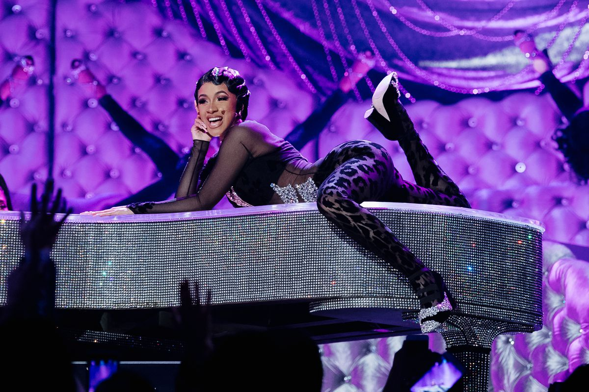 Singer Cardi B singing from atop a rhinestone-covered grand piano.