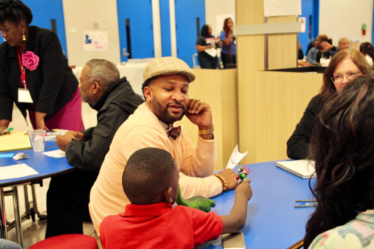 Antonio Burt talks to a young student at a state-led listening tour at Wooddale High School.
