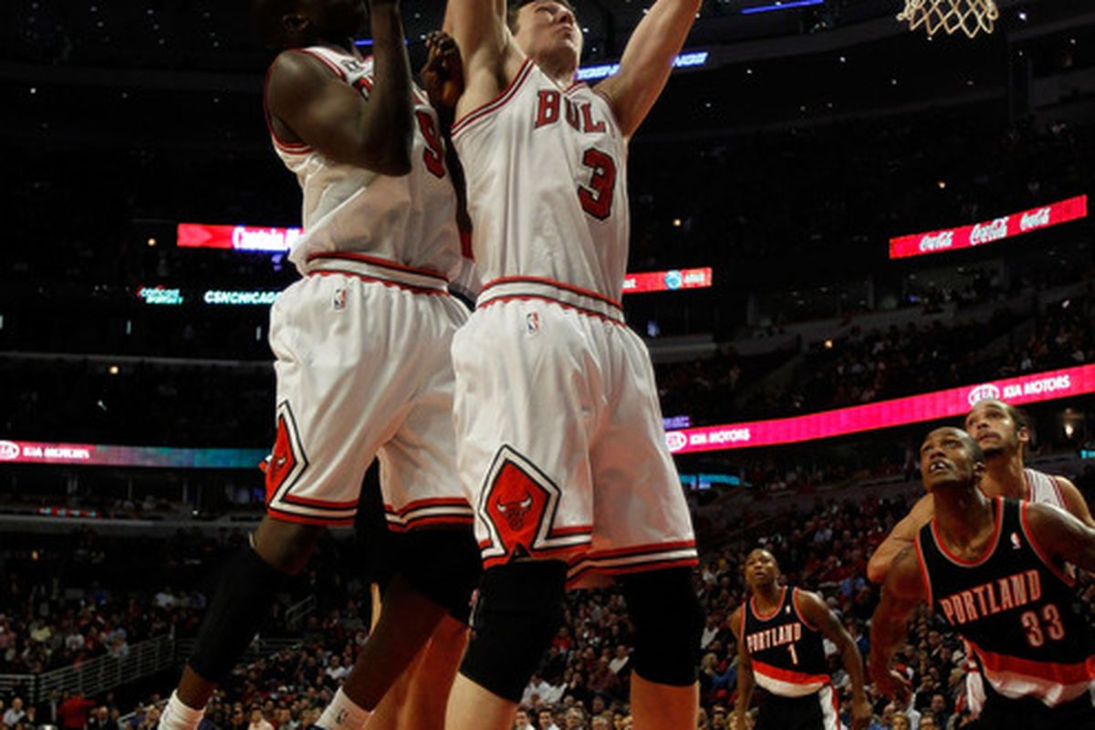Omer Asik of the Bulls leaps over teammate Luol Deng to grab a rebound against the Portland Trail Blazers at the United Center on November 1 2010 in Chicago Illinois. (Photo by Jonathan Daniel/Getty Images)