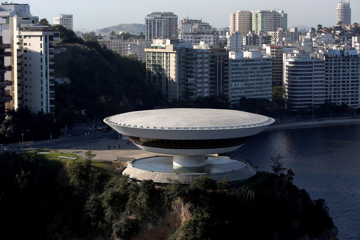 The exterior of the Niteroi Contemporary Art Museum. The building is sauced shaped and situated on a rock bed. There is water surrounding the building. In the distance is a city skyline with tall buildings.