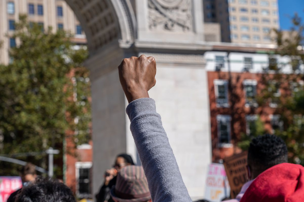 A protester's raised fist in front of the arch in Washington Square Park.