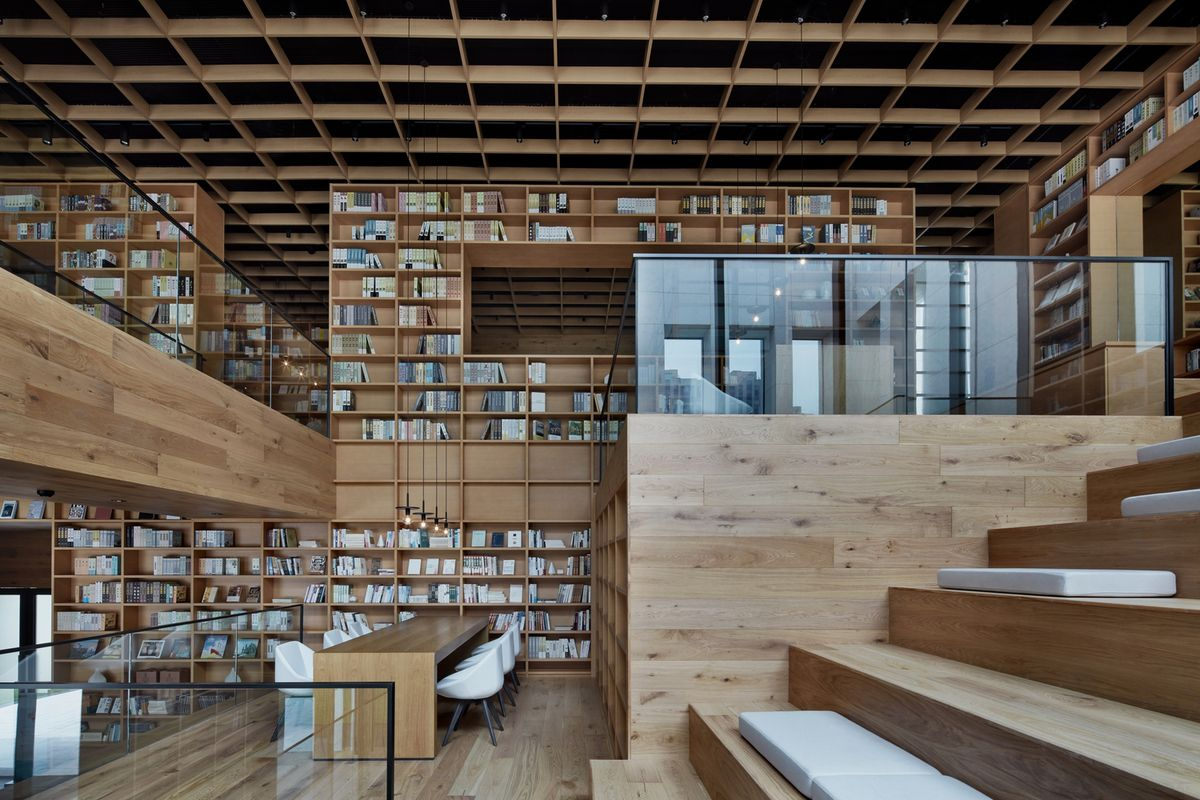 Platform stairs made from light timber contain seating. The area is surrounded by full height timber shelves filled with books.
