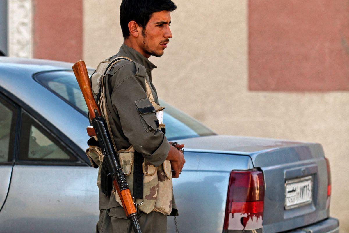 A Kurdish soldier in Kobane, with dog.