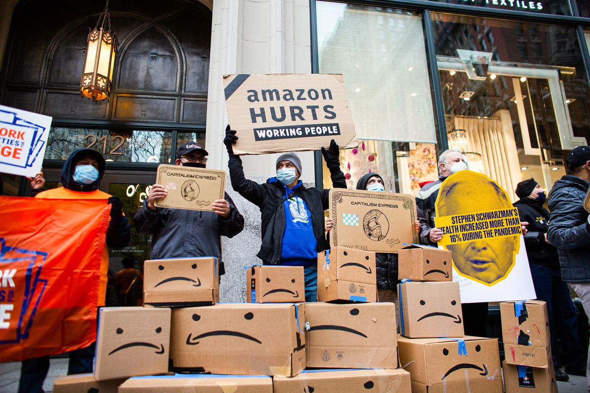 """Amazon workers demonstrating in front of the Jeff Bezos's house, with a sign reading """"Amazon hurts working people."""""""