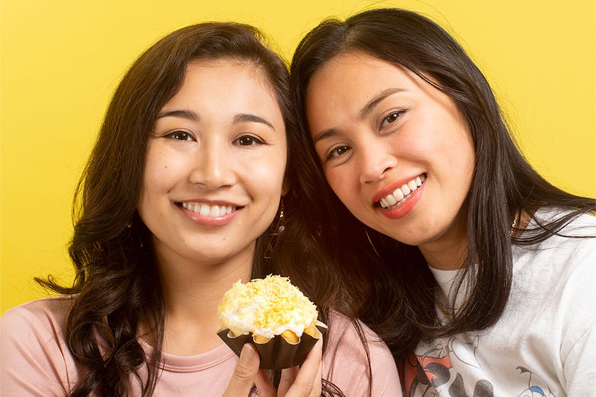 Carla Chavez holds a cheese ensaymada in her hand. Ada Chavez leans her head against her sister's.