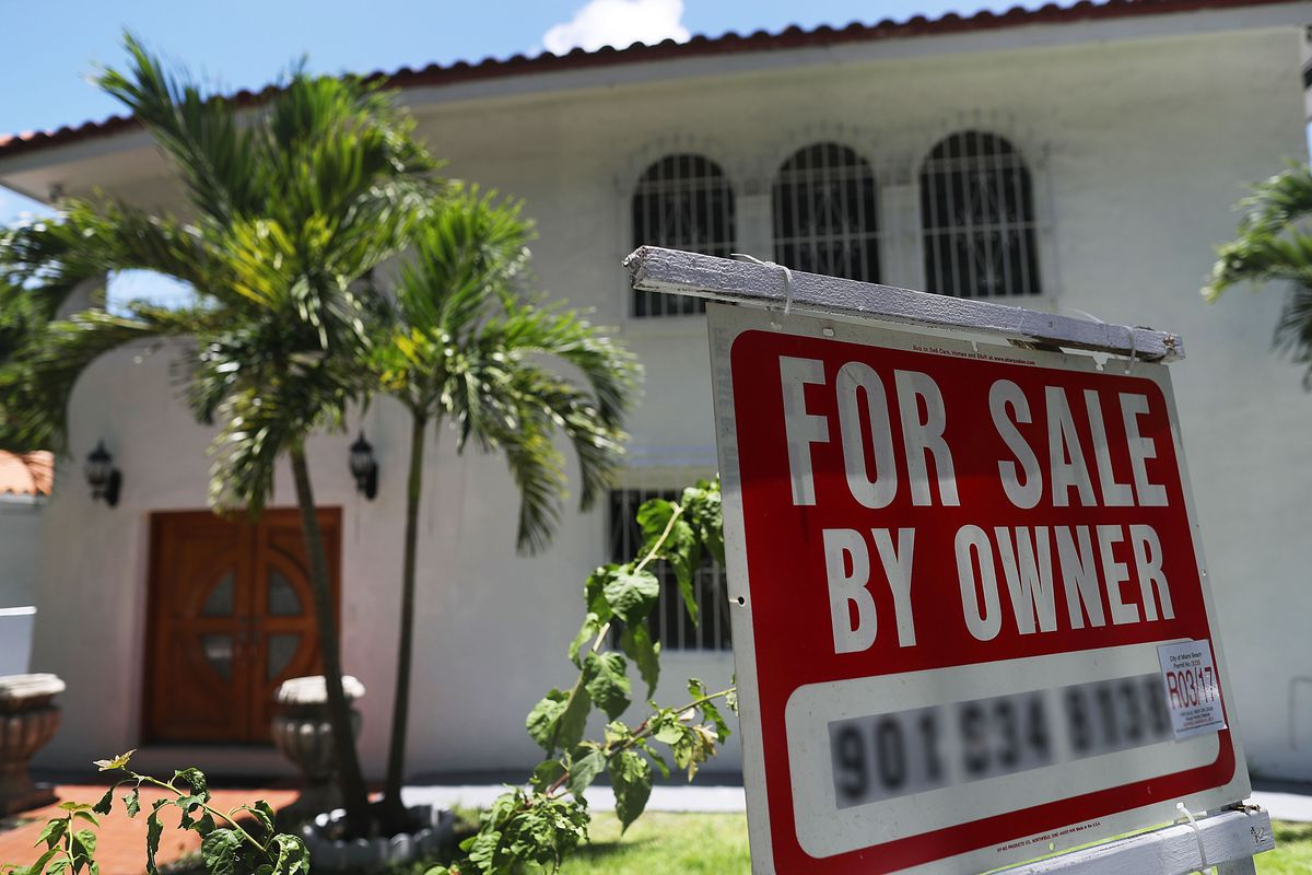A for-sale sign is seen in front of a home in Miami,