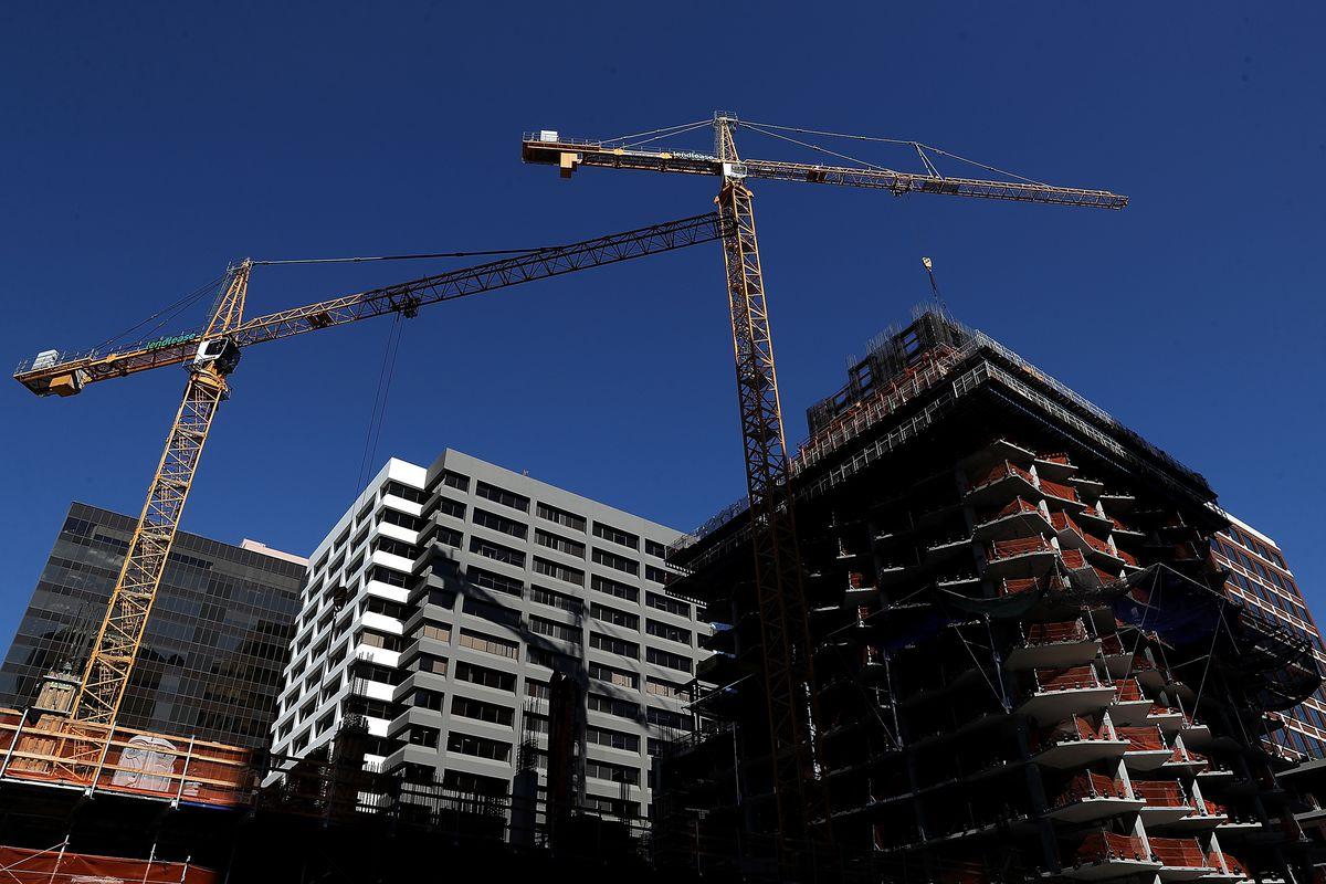 Construction cranes hang over a building under construction.