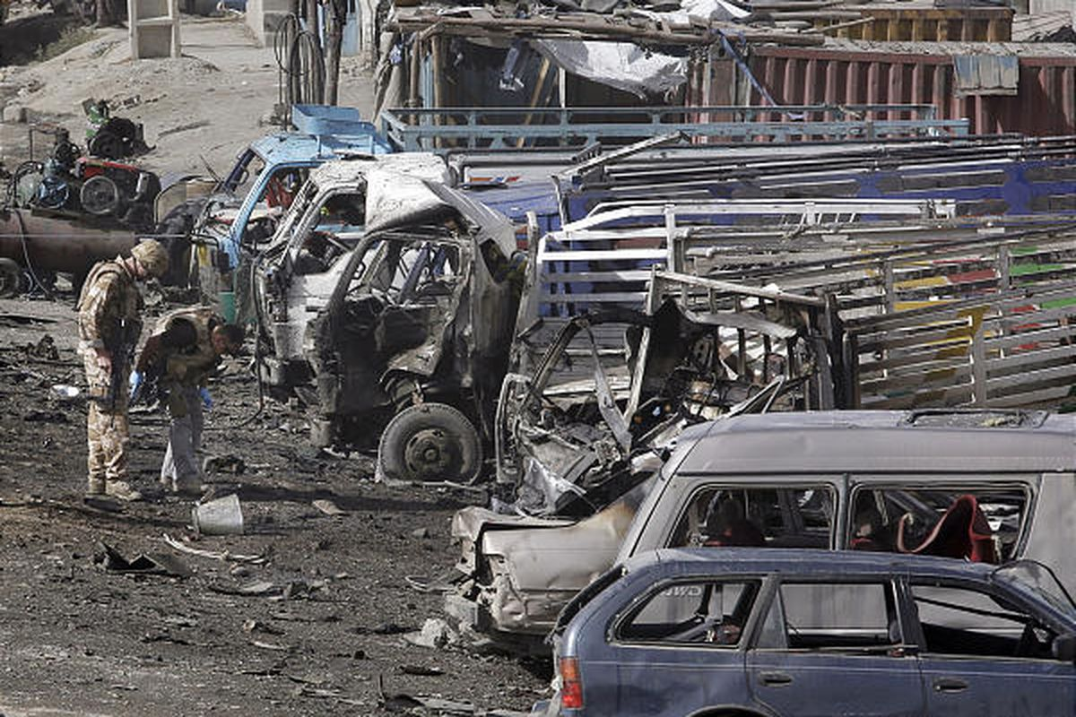 British soldiers gather evidence next to destroyed cars at the scene of a suicide car-bomb attack outside Kabul.