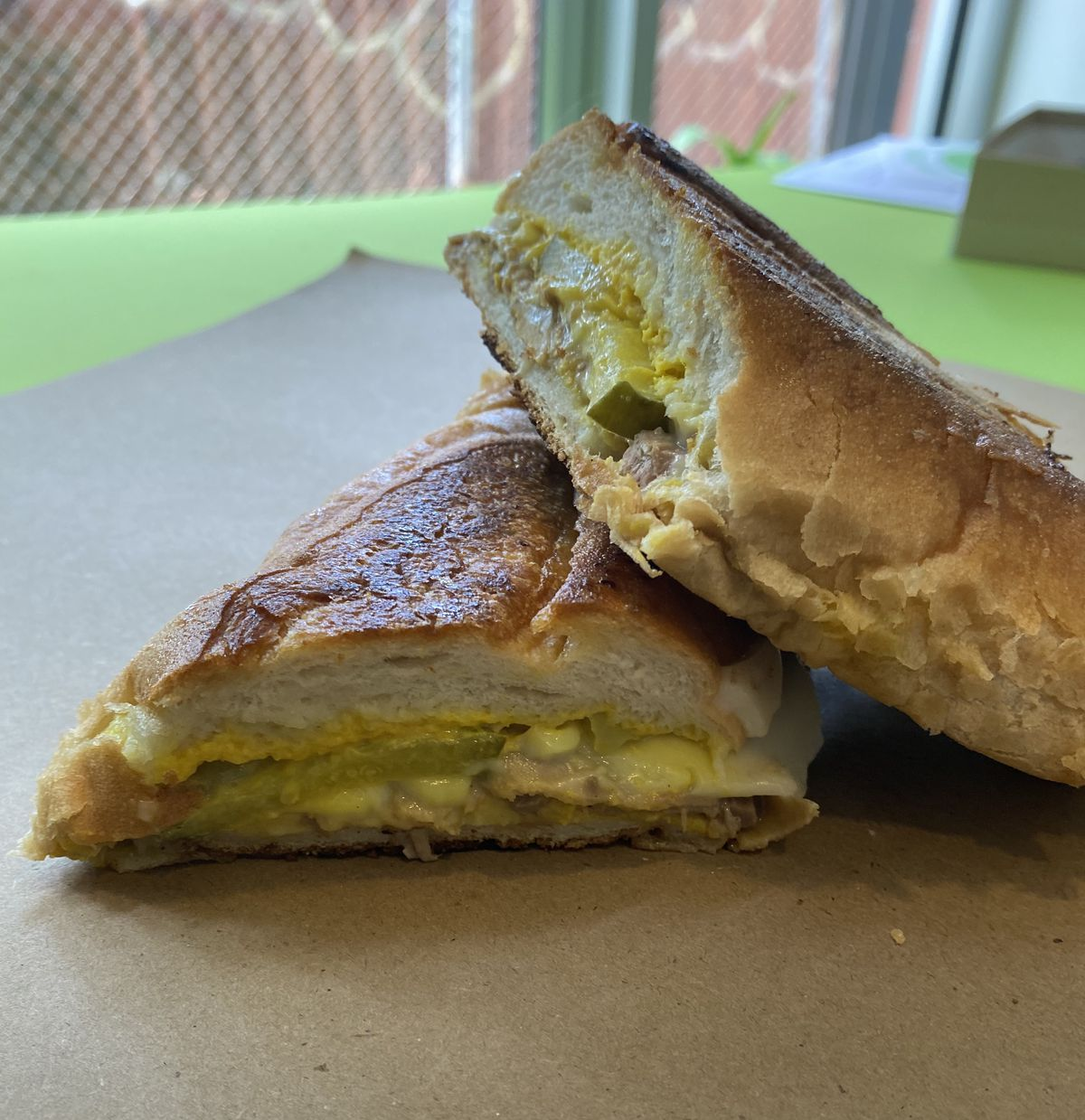Two halves of a sandwich rest on top of one another are are filled with what appears to be eggs, cheese, and pickles