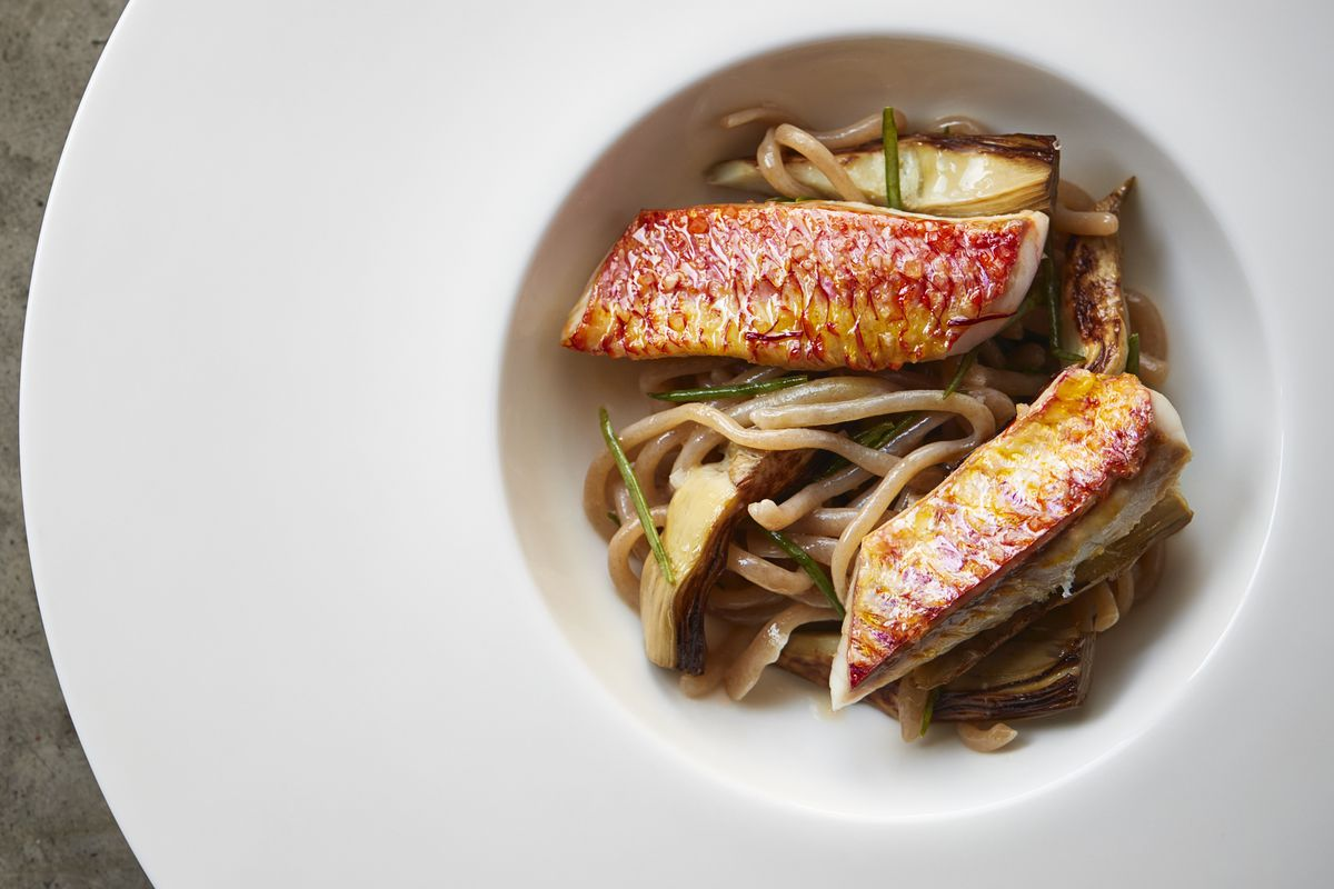 Red mullet with pici pasta and artichokes in a deep, white presentation bowl
