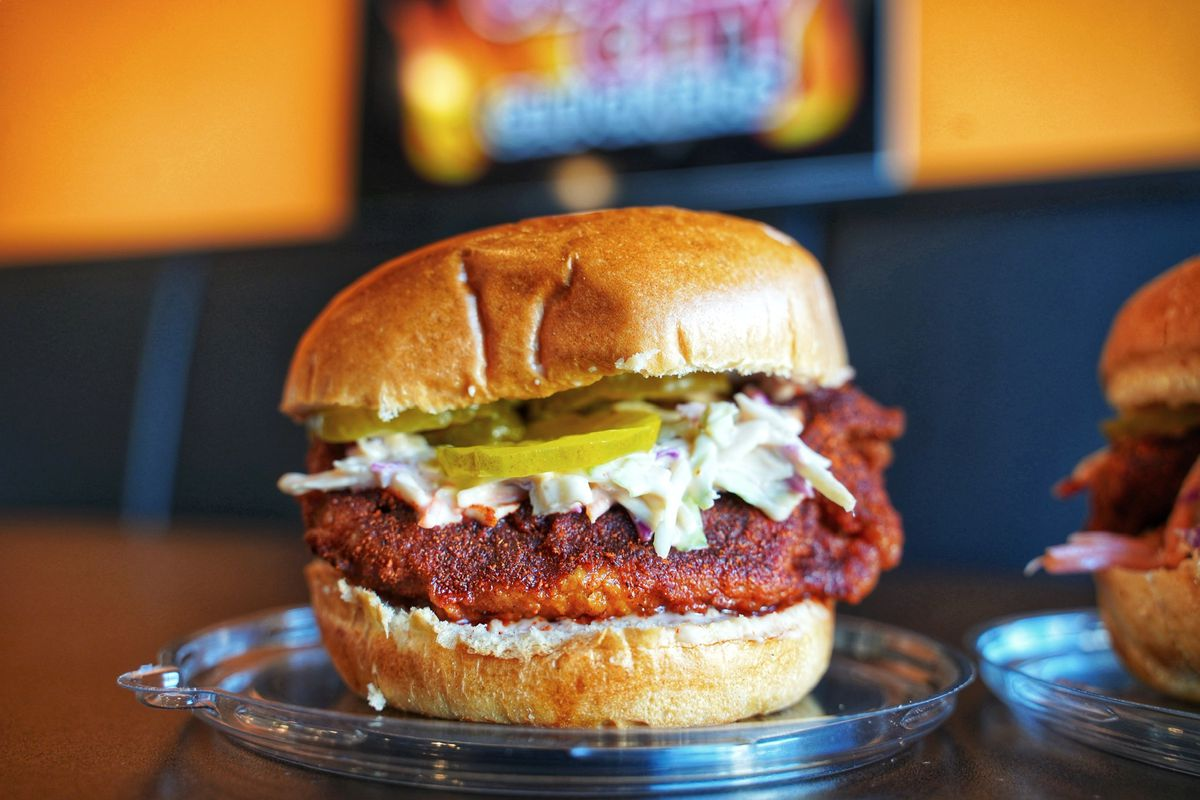a hot chicken sandwich with deep reddish-brown breading served on a bun with a healthy dollop of cole slaw