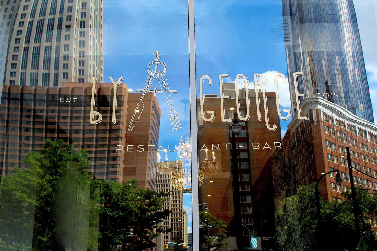 The stenciled restaurant name on the window of the Candler Hotel with downtown buildings like the Omni reflected in the background