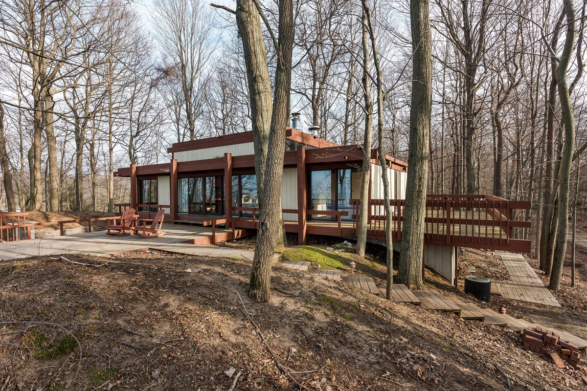 Post-and-beam wooden house with large glass windows and decking surrounded by woods.