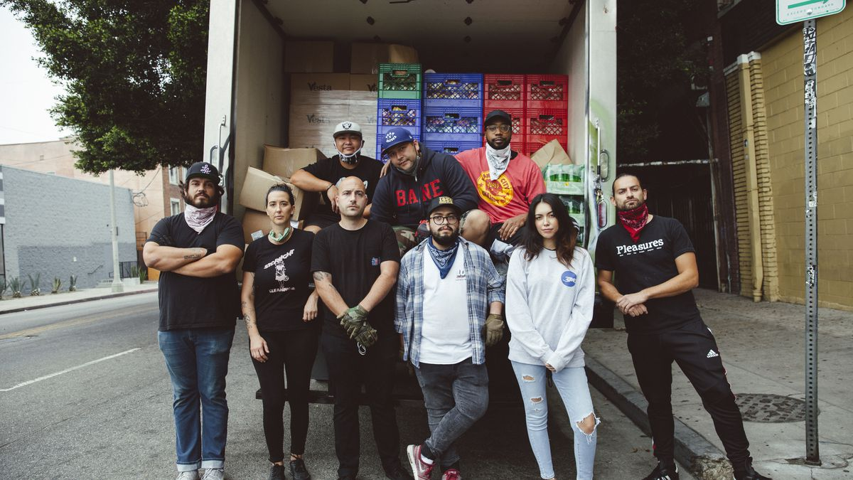 Nine people standing in front of an open truck containing crates of donated food.