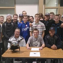 Easton Walker surrounded by his teammates and HS coaches.