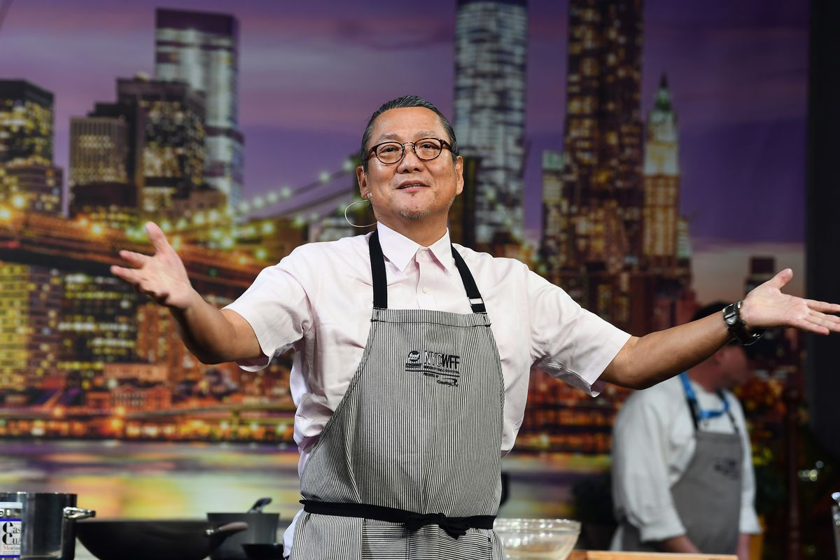 Chef Masaharu Morimoto on stage at the New York City Wine and Food Festival opening his arms  in front of a backdrop of the Brooklyn Bridge.