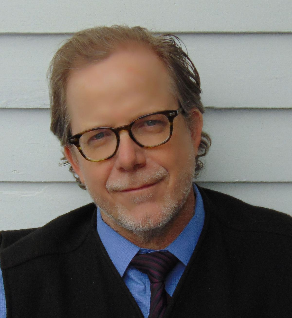 A man in glasses and a dark tie sits against a walls.