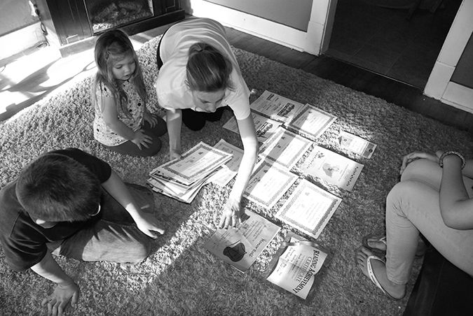 Julianne Williamson spreads out her children's academic awards from the Bessemer Academy in her living room in Pueblo. With her are her children Trinity, who will enter kindergarten this upcoming school year, Jacob, a third grader, and Ryane.