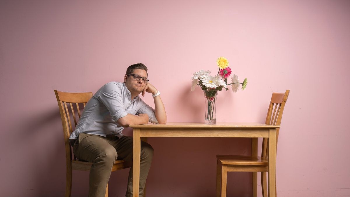 Alex Falcone, a man with glasses and a button-up, sits at a wooden table alone in front of a pink wall.