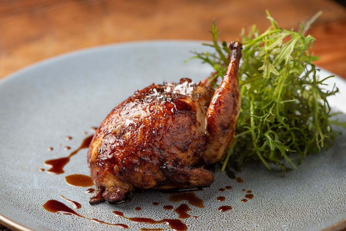 Small roasted quail in light sauce with greens on a grey plate.