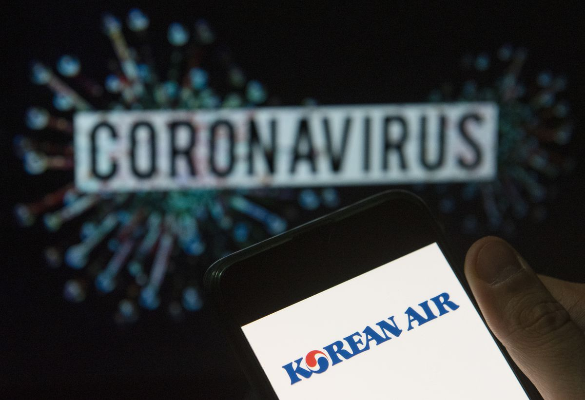 In this photo illustration the airline and flag carrier of South Korea, Korean Air, logo seen displayed on a smartphone with a computer model of the COVID-19 coronavirus on the background.