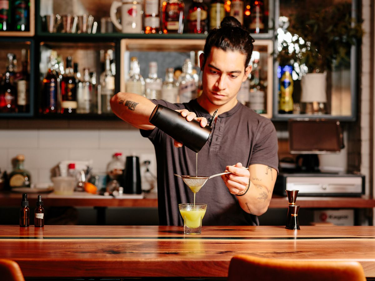 A bartender strains a cocktail from a shaker through a fine mesh strainer into a lowball glass in front of a backbar filled with bottles