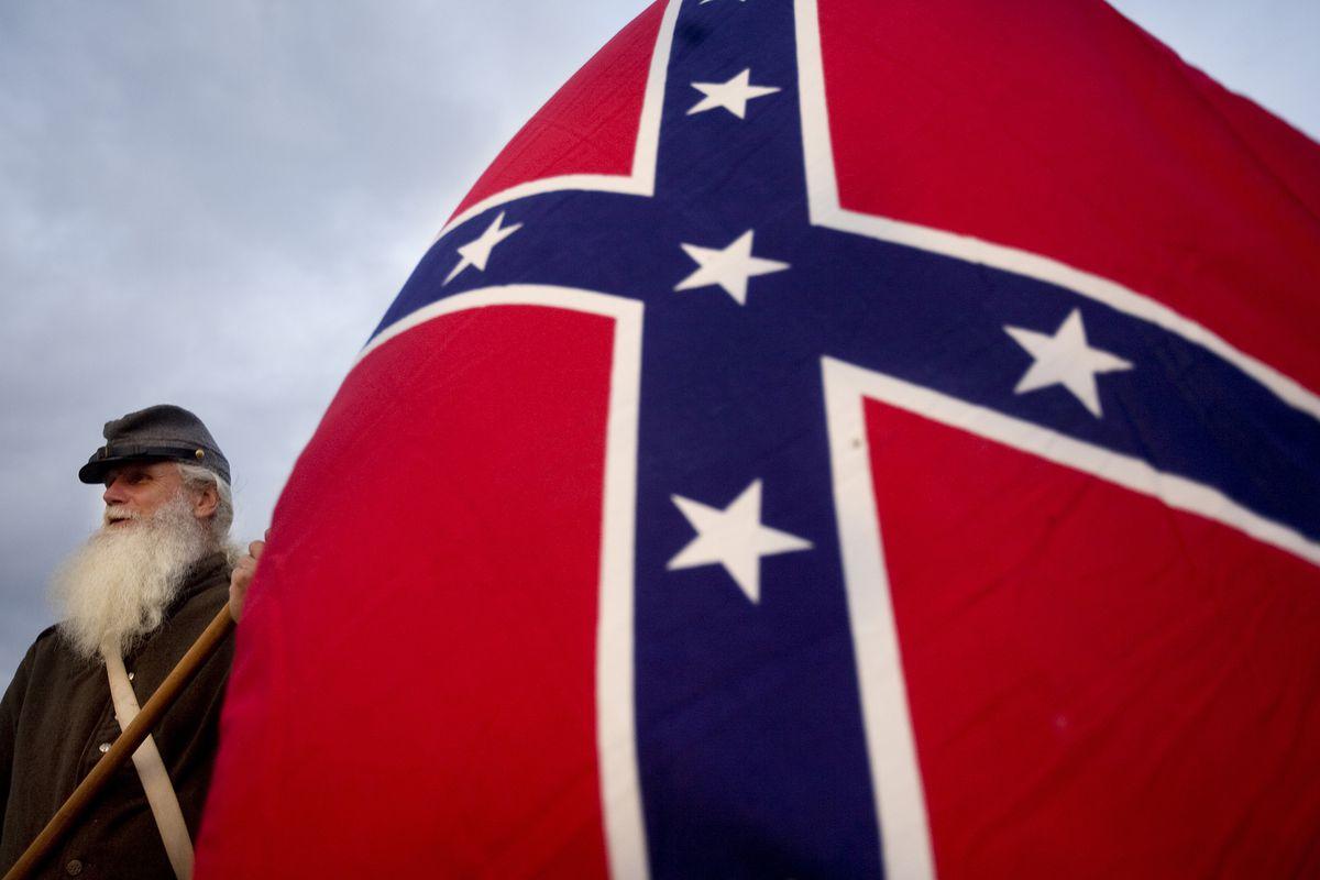 A Civil War reenactor with a Confederate flag in South Carolina.