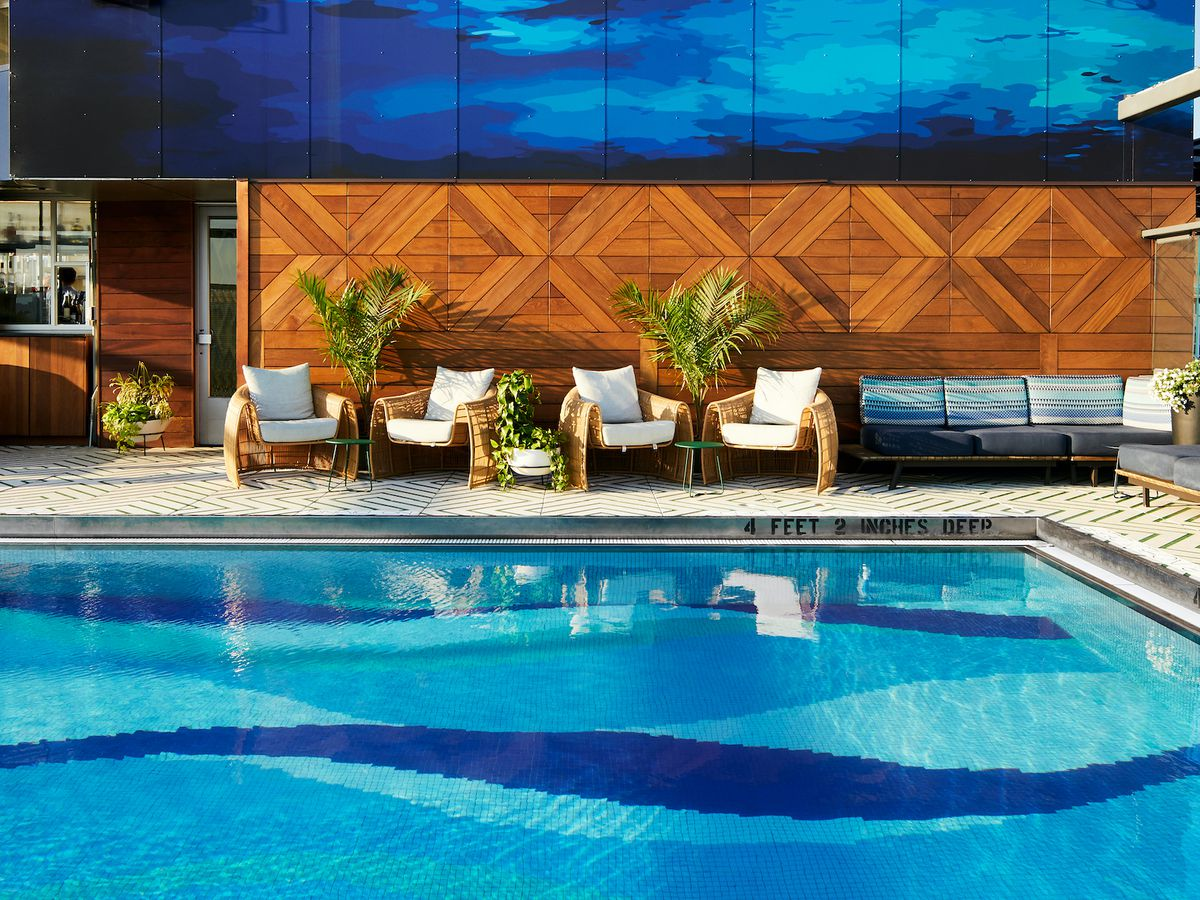 Outdoor furniture is set up around a pool with a patterned floor. In the background is a bar.