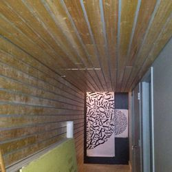 Wood-clad low ceilings give the feeling of a sauna to this passageway