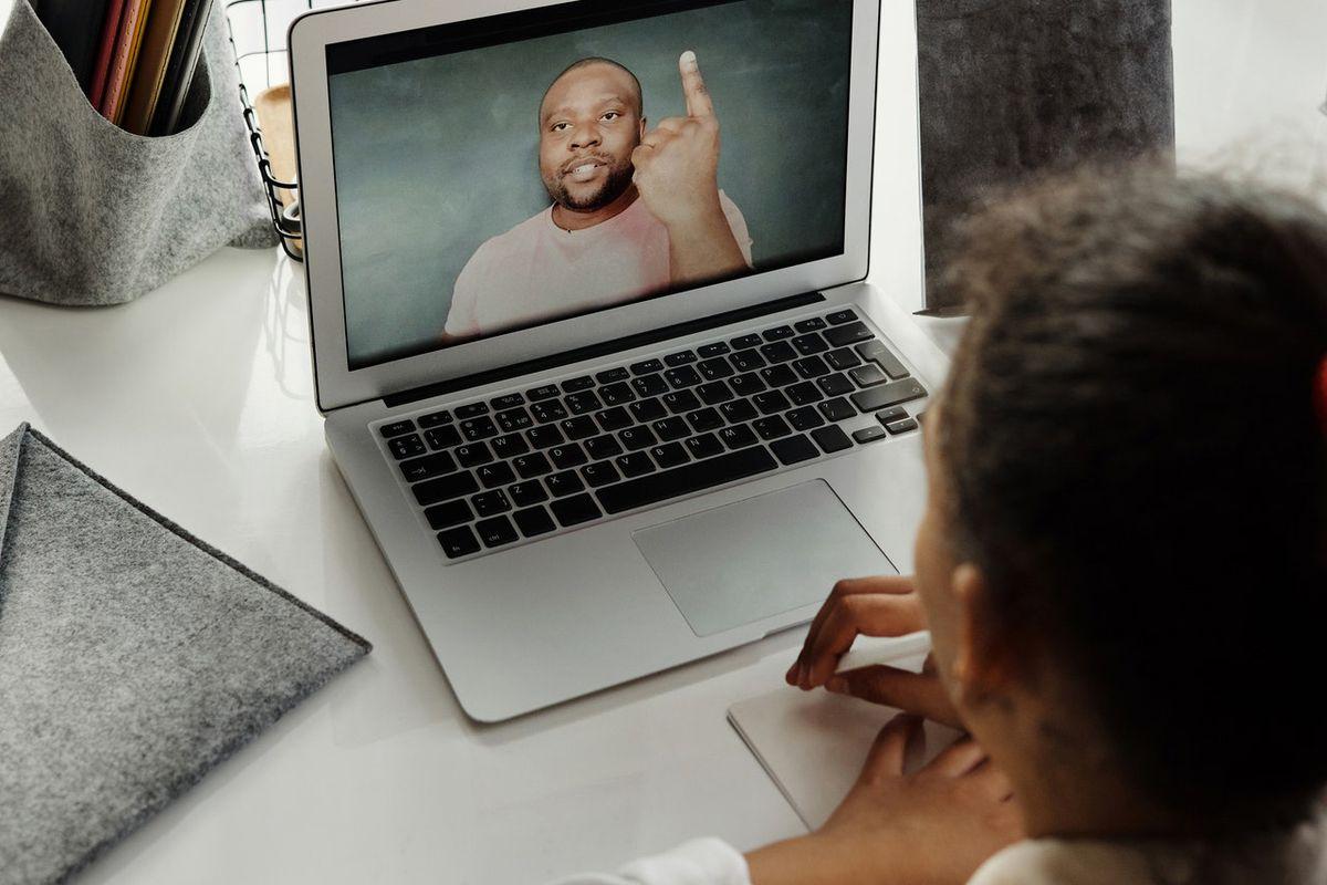 Student watching her teacher on a laptop.