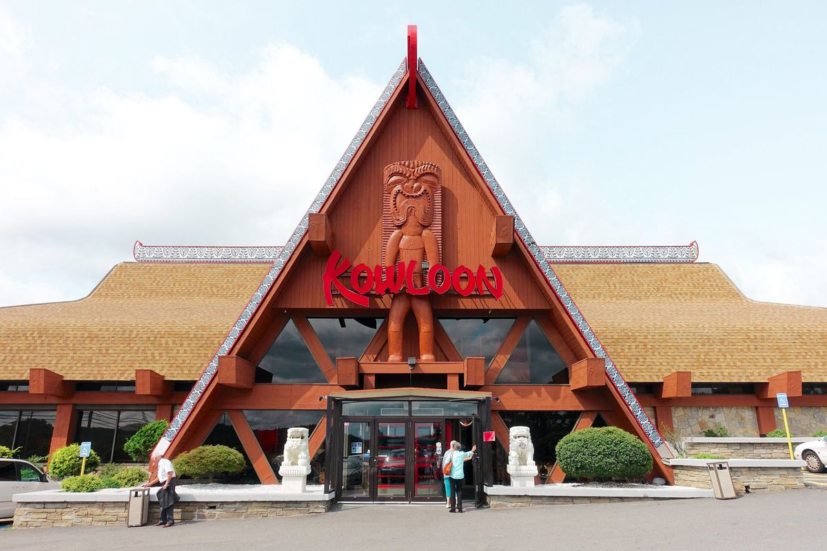Exterior view of a restaurant with a large A-frame entrance and red signage