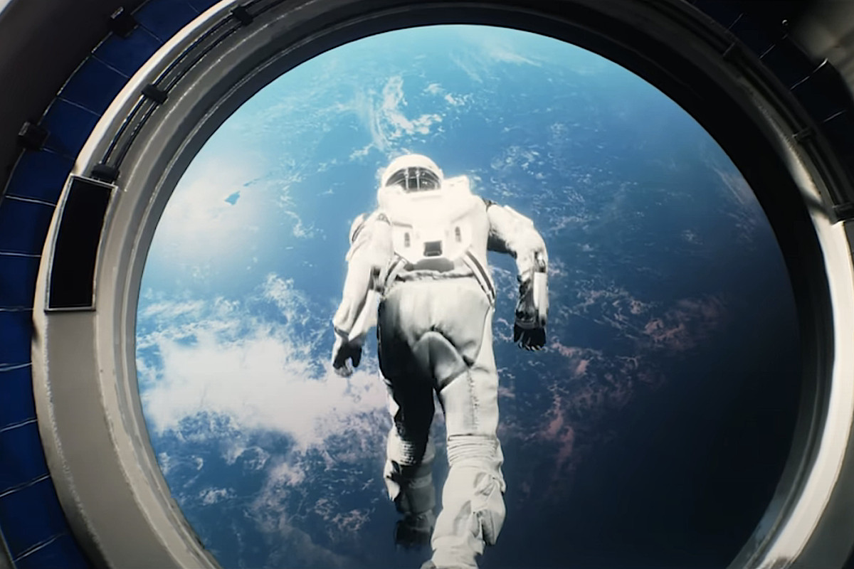 A man in a spacesuit, silhouetted against Earth, leaps through of a portal into space in Warning