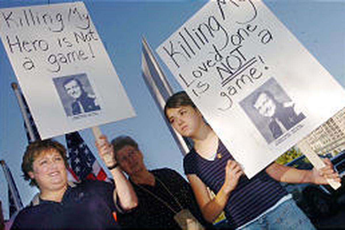 """Brenda Lund, left, and niece Kelliann Crowell, 13, join others outside Avalanche Video to protest the video game """"25 to Life"""" on Monday. Lund's husband, a UHP troop, was shot and killed in the line of duty in 1993 in Green River."""