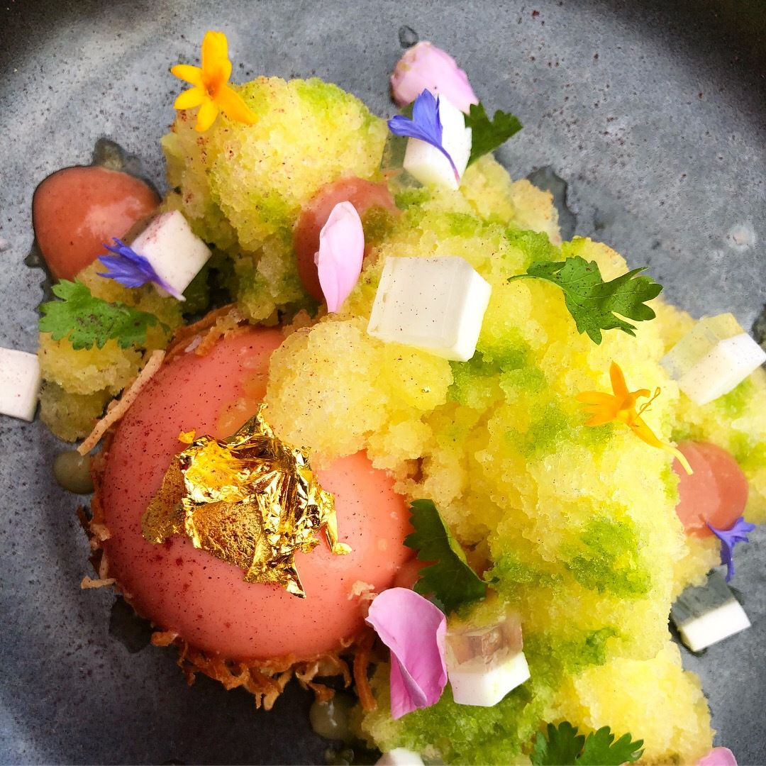 A picture of a round, pink mousse topped with gold leaf, clouds of pineapple ice, and scattered edible flowers and herbs at Departure