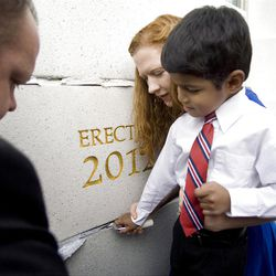 Angela Christensen helps her son Josh apply mortar to the cornerstone as crowd members were invited to participate.