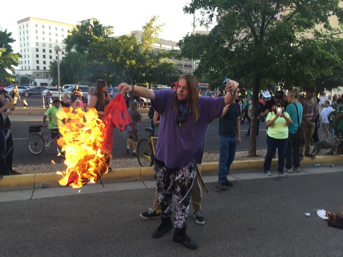 A protester holds a burning T-shirt as hundreds of people protest outside Trump's rally.   Russell Contreras/AP